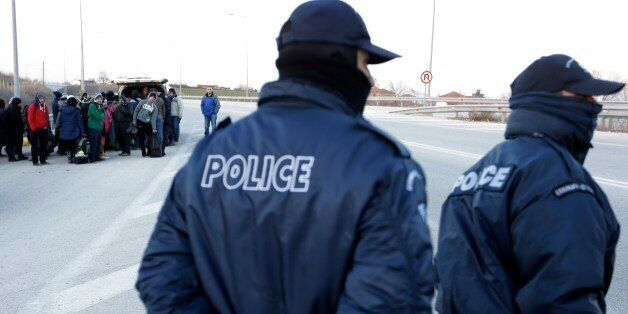 Refugees and migrants embark in a police van as policemen patrol on a highway near the northeastern Greek...