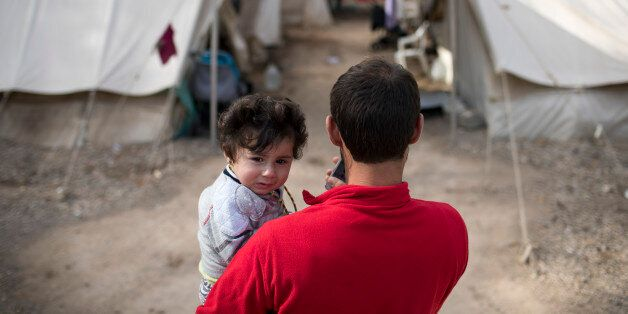 A Syrian man holds his eight month old daughter at Ritsona refugee camp north of Athens, on Wednesday,...