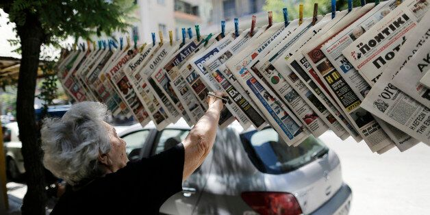 A woman reaches for a newspaper at a news kiosk in Thessaloniki, Greece, on Sunday, July 12, 2015. European...