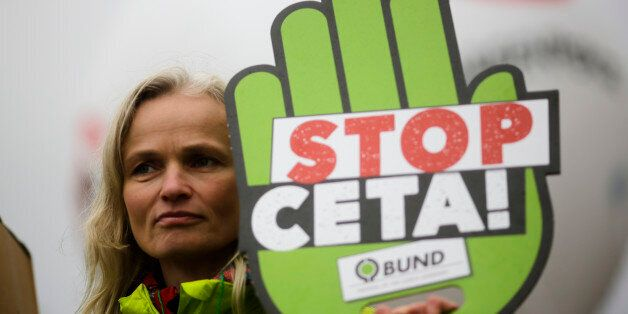 A demonstrator holds a poster against the Comprehensive Economic and Trade Agreement, CETA, during a...