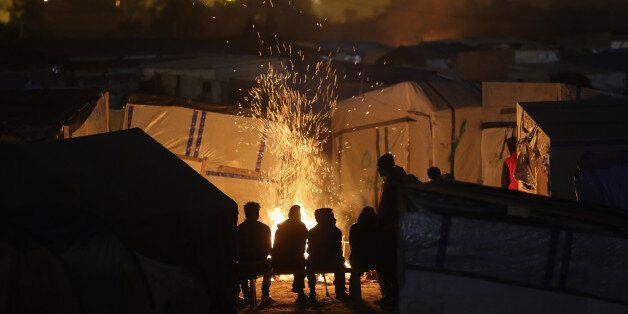 CALAIS, FRANCE - OCTOBER 24: Migrants sit by a fire inside the Jungle camp on October 24, 2016 in Calais,...