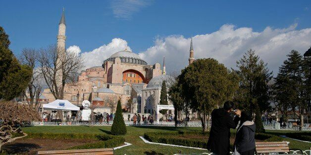 Tourists take pictures of the Byzantine-era Hagia Sophia, near the site of Tuesday's explosion, in the...