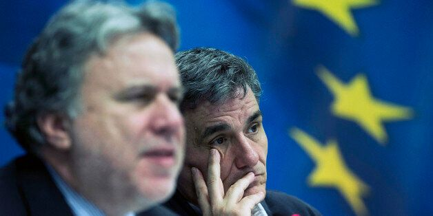 Greek Finance Minister Euclid Tsakalotos, right, listens as Labour Minister George Katrougalos talks...