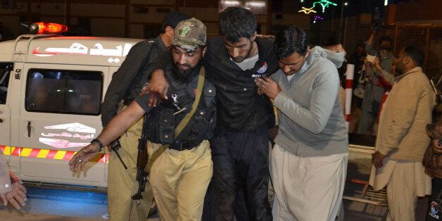 A Pakistani volunteer and a police officer rush an injured person to a hospital in Quetta, Pakistan,...