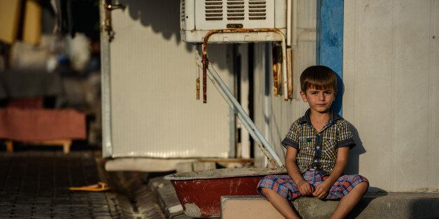 A Syrian child sits at a refugee camp in the Kilis district of Gaziantep, southeastern Turkey, on October...