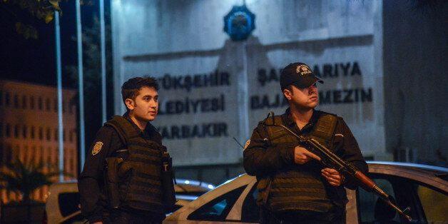 Armed Turkish anti riot police officers stand in front of the Diyarbakir's municipality headquarters...