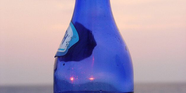 A half full blue bottle of water in front of a red sunset on the island of Lefkada, in