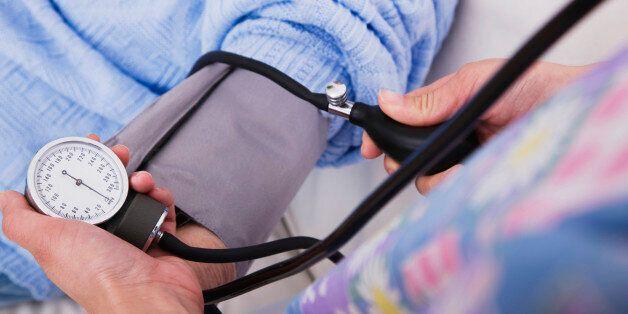 Close-up of female nurse taking senior woman's blood pressure