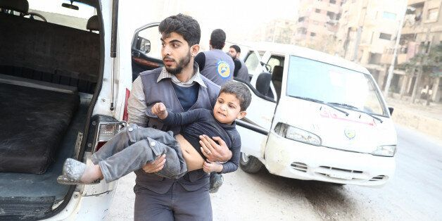 A member of the Syrian Civil Defence, known as the White Helmets, evacuates a child following reported...