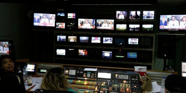 Journalists operate at the master control of ERT following the public broadcaster's re-launch in Athens,...