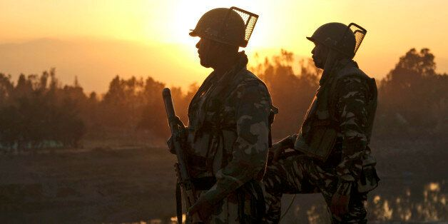 Indian soldiers stand guard near a building where suspected militants have taken refuge during a gun...