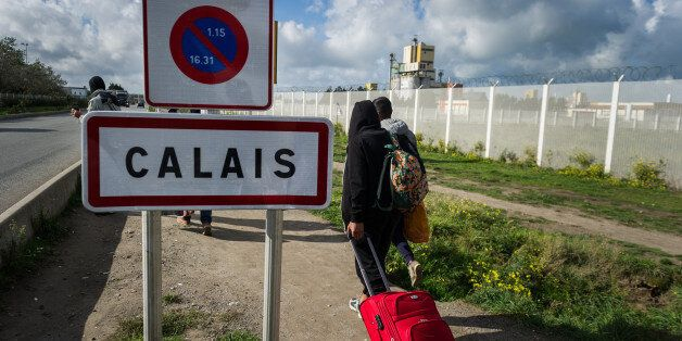 Migrants pass on their way out of the Calais Jungle the town sign of Calais. The refugee camp on the...