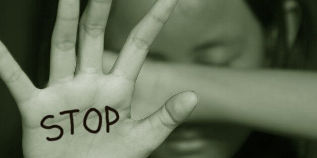 Little girl suffering bullying raises her palm asking to stop the violence in sepia