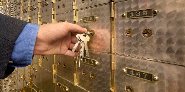 Man's hand holding key to safety deposit box,