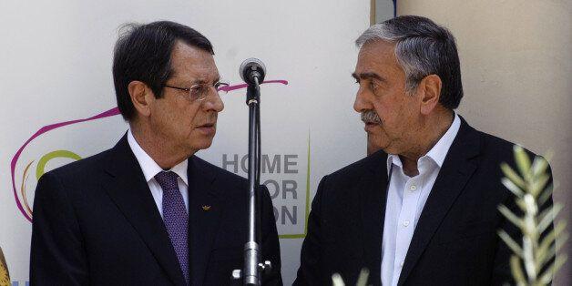 Greek Cypriot President Nicos Anastasiades (L) and Turkish Cypriot leader Mustafa Akinci (R) talk during...