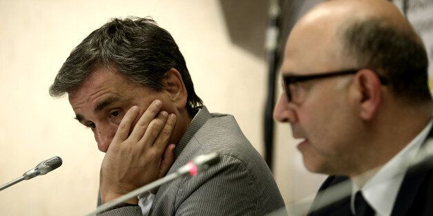 Greek Finance Minister Euclid Tsakalotos (L) during a joint press conference with Pierre Moscovici, European...