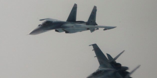 Two Russian Su-27 fighter jets fly next to a civilian airplane playing the role of a hijacked airliner,...