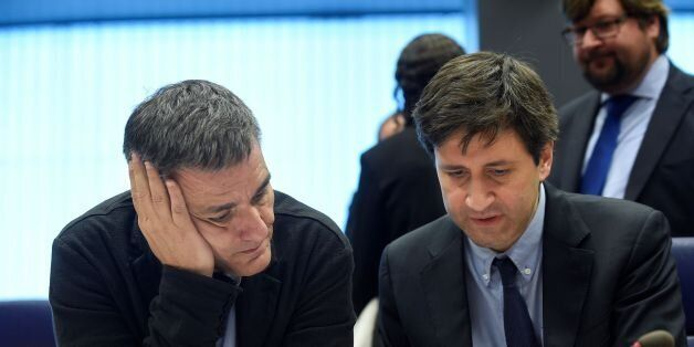 Greek Finance Minister Euclid Tsakalotos (L) listens to a Greek advisor during an Eurogroup meeting in...