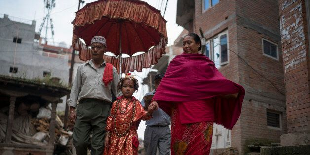 BHAKTAPUR, NEPAL - OCTOBER 07: The Kumari priest and his wife escort Jibika Bajracharya, the newly appointed...