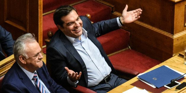 Prime Minister Alexis Tsipras smiles in the Hellenic Parliament during parliamentary dispute at level...