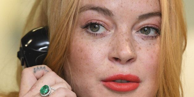 U.S. actress Lindsay Lohan speaks on a telephone as dealers work on a trading floor during a charity...