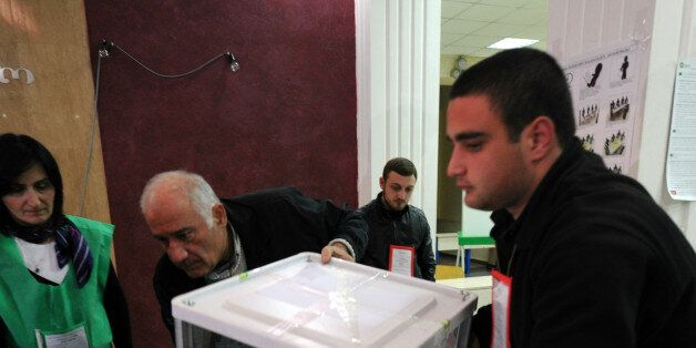 Members of the Georgian election committee carry a ballot box after voting closed at a polling station...