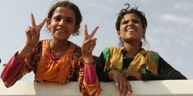 Displaced Iraqi girls from Qayyara sit in a vehicle belonging to Iraqi security forces, as they transfer...