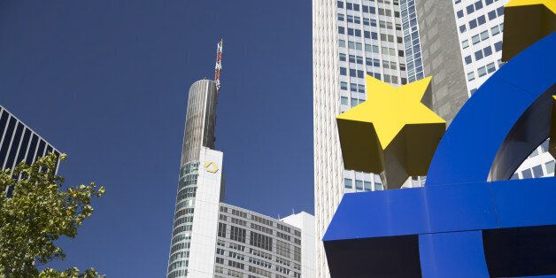 The Commerzbank AG headquarters, center, stands behind the euro sign sculpture in Frankfurt, Germany,...