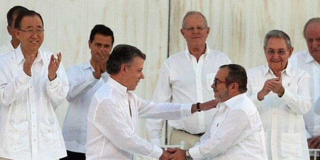 Colombia's President Juan Manuel Santos, front left, and the top commander of the Revolutionary Armed...