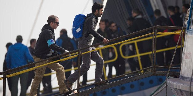 An officer from the European Union's border protection agency, Frontex, leads a migrant to board a...