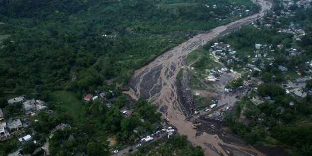 People gather next to a collapsed bridge after Hurricane Matthew passes Petit Goave, Haiti, October 5,...