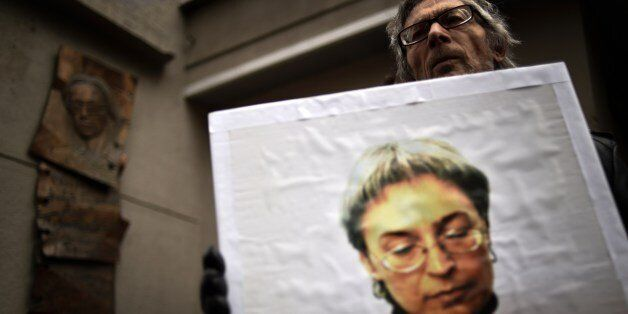 A man holds a portrait of slain Russian journalist Anna Politkovskaya during a rally marking the 8th...