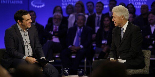 Prime Minister of Greece Alexis Tsipras (L) speaks with former President Bill Clinton during the Clinton...