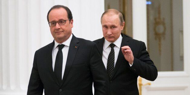France's President Francois Hollande, left, and Russian President Vladimir Putin enter a hall for their...