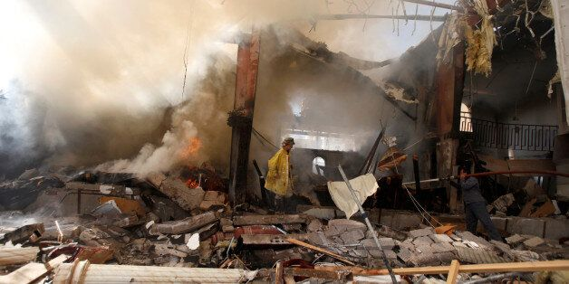 Firefighters try to extinuish fire at the community hall where Saudi-led warplanes struck a funeral in...