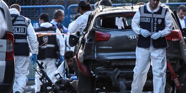 Forensic officers work next to damaged motorbike at the scene of a blast near a police station in Istanbul...