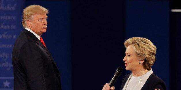 Republican presidential nominee Donald Trump listens to Democratic presidential nominee Hillary Clinton...