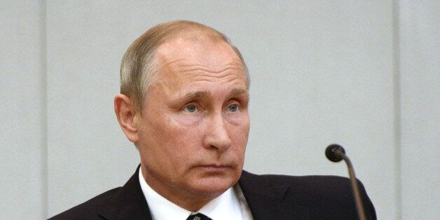 Russian President Vladimir Putin listens during the opening session of the newly elected State Duma,...
