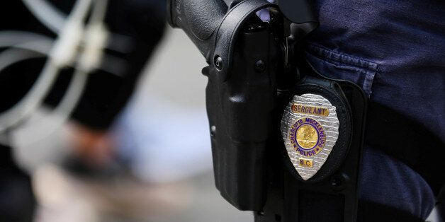 The badge and gun of a Charlotte police officer in riot gear are seen during a large security presence...