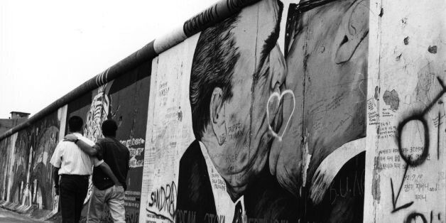 A gay couple strolling past graffiti on the Berlin Wall depicting German leaders Leonid Brezhnev and...