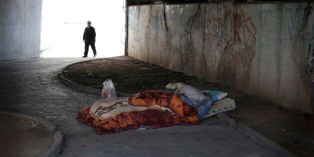 A homeless man sleeps under a bridge as an elderly woman walks past in Athens, Thursday March 19, 2015....
