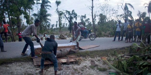 EDS NOTE GRAPHIC CONTENT- Residents try to put the body of victim of Hurricane Matthew in a coffin in...