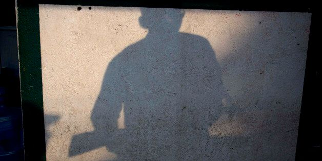 In this Thursday, Jan. 16, 2014 photo, the shadow of an armed man, who belongs to the Self-Defense Council...