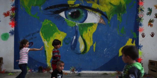 In this photo taken on Tuesday, Sept. 13, 2016, children play in front of a mural at Ritsona refugee...