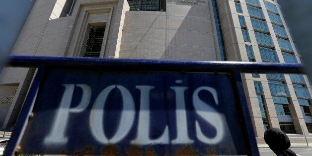 A woman enters a courthouse as a police fence is on display outside the building in Istanbul, on Monday,...