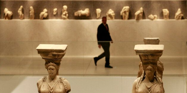 A security guard walks past Caryatid statues during the official opening ceremony of the New Acropolis...