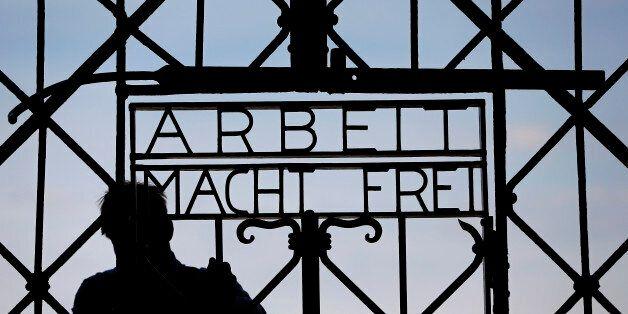 A blacksmith prepares a replica of the Dachau Nazi concentration camp gate, with the