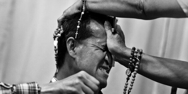 BOGOTA, COLOMBIA - MARCH 10: A Colombian pastor, pressing a crucifix on a believer's head, attempts to...