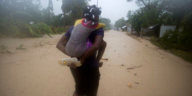 A woman and a child walk in a waterlogged street as they head to a shelter under the pouring rain caused...