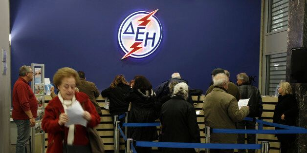 Consumers wait in line at a public office of Greece's public power corporation (PPC) in Athens November...